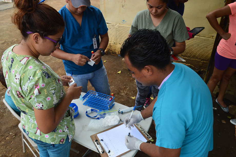 Photo of study personnel preparing to collect blood samples from children in a neighborhood in Managua in June 2017